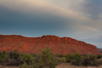 To the east, the red cliffs glow with the sun's last rays